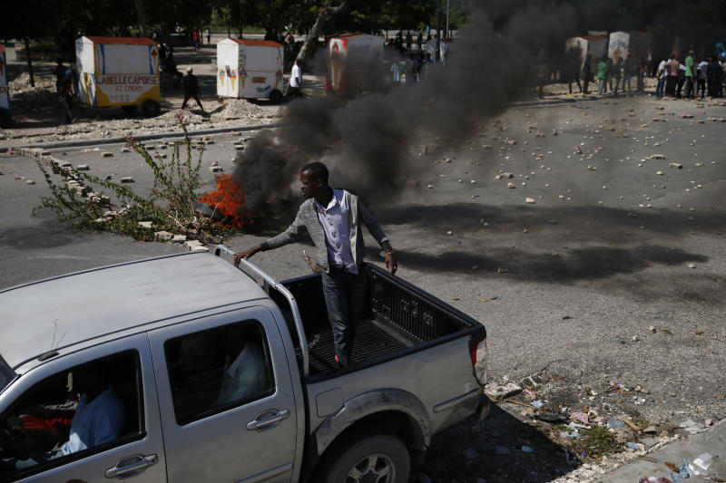 A presidential convoy drives past a burning barricade in Port-au-Prince, Haiti, Monday, Oct. 7, 2019. Opposition leaders are asking supporters to gather Monday in front of the National Palace to demand the resignation of President Jovenel Moise, who had been scheduled to attend an official ceremony nearby. (AP Photo/Rebecca Blackwell)