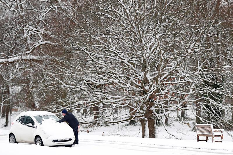 A motorist clears snow from the windscreen of a car in Hartley Wintney, in Hampshire, 40 miles west of London, on February 1, 2019. - Snowfall and icy conditions were expected Friday to cause travel disruption after temperatures overnight reached as low as minus 15.4C. An amber snow warning has been issued for an area west of London including parts of Oxfordshire, Hampshire and Buckinghamshire, after as much as 14cm of snow fell on south-west England. (Photo by Adrian DENNIS / AFP) (Photo credit should read ADRIAN DENNIS/AFP via Getty Images)