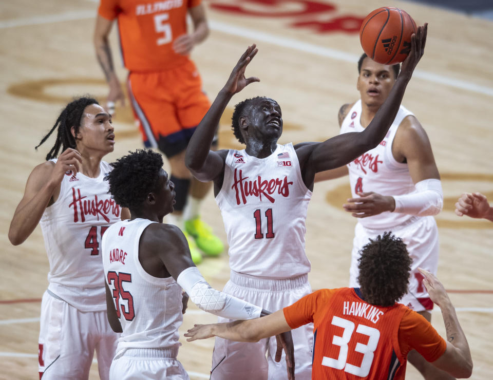 Nebraska forward Lat Mayen (11) pulls in a defensive rebound next to Illinois' Coleman Hawkins (33) during the first half of an NCAA college basketball game Friday, Feb. 12, 2021, in Lincoln, Neb. (Francis Gardler/Lincoln Journal Star via AP)
