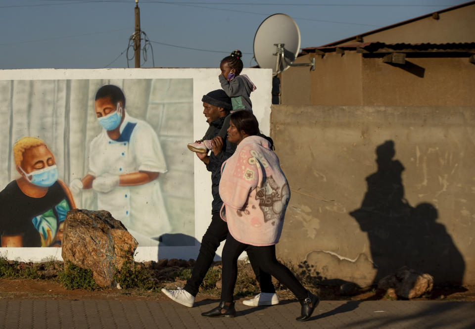 FILE - In this June 23, 2021, file photo, a family walks past a mural promoting vaccination for COVID-19 in Duduza township, east of Johannesburg, South Africa. New infections in South Africa rose to record levels in recent days, part of a rapid rise across the continent, and experts say the surge here has not yet peaked. South Africa reimposed several restrictions, and its vaccination drive is finding its feet after several stumbles. But even as the campaign gathers pace, experts say it's too late to reduce the deadly impact of the current spike. (AP Photo/Themba Hadebe, File)