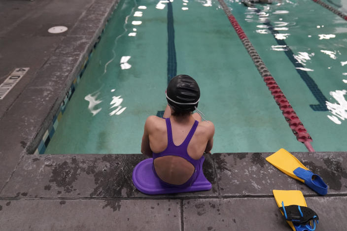 """A proposed ban on transgender athletes playing female school sports in Utah would affect transgender girls like this 12-year-old swimmer seen at a pool in Utah on Monday, Feb. 22, 2021. She and her family spoke with The Associated Press on the condition of anonymity to avoid outing her publicly. She cried when she heard about the proposal that would ban transgender girls from competing on girls' sports teams in public high schools, which would separate her from her friends. She's far from the tallest girl on her team, and has worked hard to improve her times but is not a dominant swimmer in her age group, her coach said. """"Other than body parts I've been a girl my whole life,"""" she said. (AP Photo/Rick Bowmer)"""
