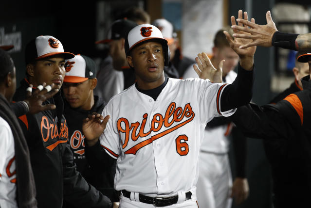 Baltimore Orioles' Jonathan Schoop high-fives teammates in the dugout after scoring on Chris Davis' single in the fourth inning of a baseball game against the Toronto Blue Jays, Wednesday, April 11, 2018, in Baltimore. (AP Photo/Patrick Semansky)