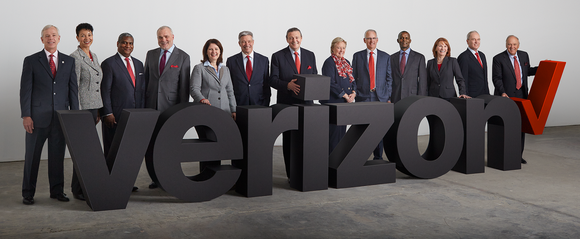 13 executives standing behind the Verizon logo.