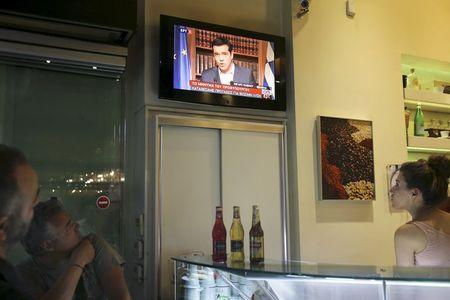An employee (R) and customers of a coffee shop follow Greek Prime Minister Alexis Tsipras live television address in Athens, Greece, July 1, 2015. REUTERS/Alkis Konstantinidis