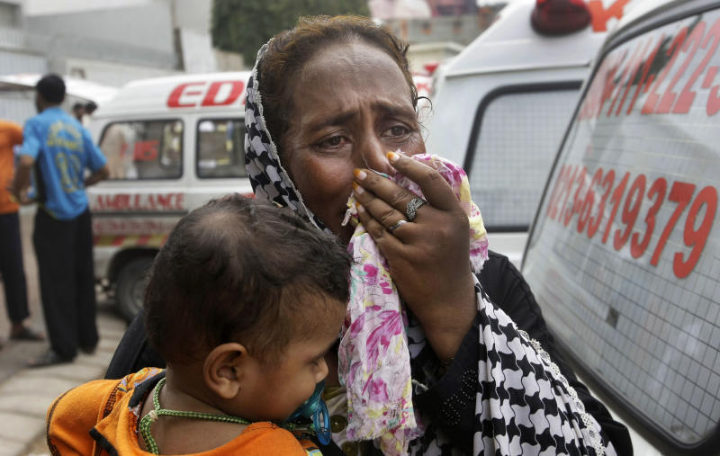 A Pakistani woman mourns the death of her family member outside a mortuary in Karachi, Pakistan, Wednesday, Sept. 12, 2012. Pakistani officials say the death toll from devastating factory fires that broke out in two major cities has killed dozens. (AP Photo/Fareed Khan)