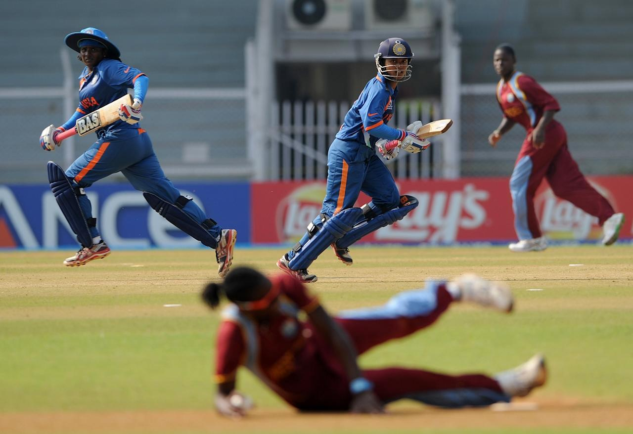 Indian cricketers Thirush Kamini (L) and  Punam Raut (C) take a run during the inaugural match of the ICC Women's World Cup 2013 between India and West Indies at the Cricket Club of India's Brabourne stadium in Mumbai on January 31, 2013. Teams from Australia, England, New Zealand, Pakistan, South Africa, Sri Lanka, West Indies join hosts India for the global event which is being played from 31 January to 17 February.  The women's World Cup opened in Mumbai with the cricketers hoping to put aside memories of the unsavoury build-up and gain their due recognition in a country where the men's game reigns supreme. AFP PHOTO/ Indranil MUKHERJEE        (Photo credit should read INDRANIL MUKHERJEE/AFP/Getty Images)