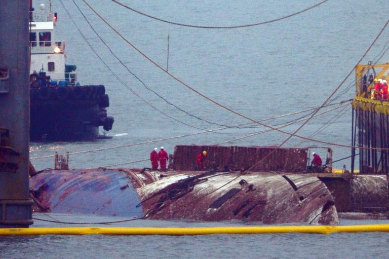 Workers check the hull of the Sewol ferry between two the barges that hauled it to the surface, nearly three years after it sank with the loss over 304 lives