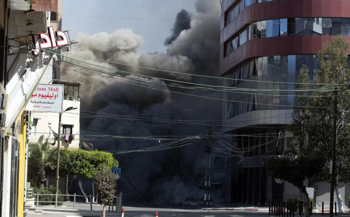 An Israeli airstrike hits the high-rise building that houses The Associated Press' offices in Gaza City, Saturday, May 15, 2021. The airstrike Saturday came roughly an hour after the Israeli military ordered people to evacuate the building. There was no immediate explanation for why the building was targeted. The building housed The Associated Press, Al-Jazeera and a number of offices and apartment. (AP Photo/Khalil Hamra)
