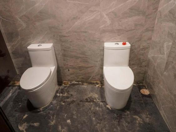 Two toilets in one cubicle at the Rizal memorial collisium in Manila (Getty)