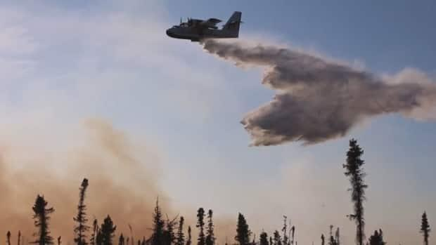 An aircraft helps extinguish a wildfire near La Ronge, Thursday.  (Don Somers/CBC - image credit)