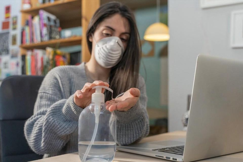 Business woman working from home wearing protective mask