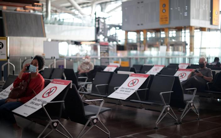 Passengers wait at the Terminal 5 departures area at Heathrow Airport in London amid coronavirus restrictions - HANNAH MCKAY/REUTERS