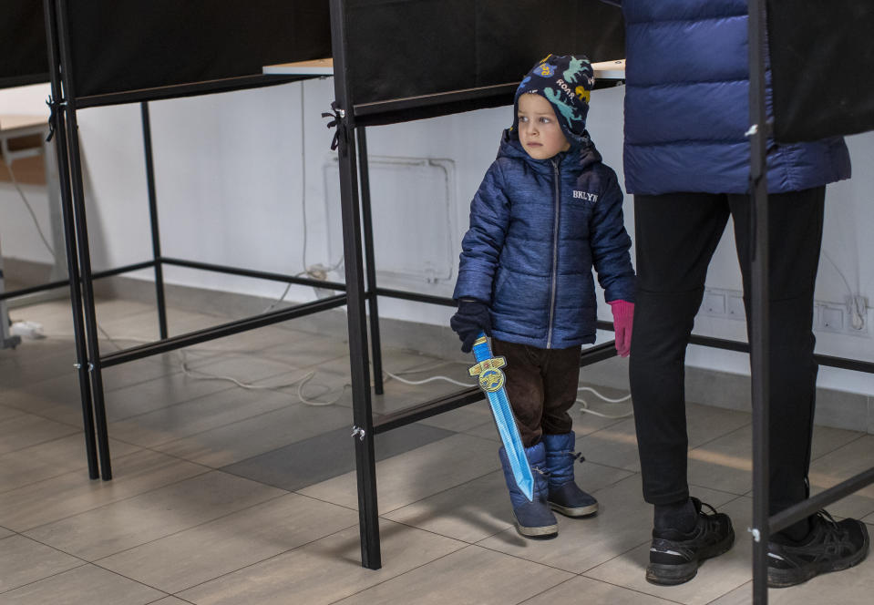 A child looks out of booth at a polling station during the second round of a parliamentary election in Vilnius, Lithuania, Sunday, Oct. 25, 2020. Polls opened Sunday for the run-off of national election in Lithuania, where the vote is expected to bring about a change of government following the first round, held on Oct. 11, which gave the three opposition, center-right parties a combined lead. (AP Photo/Mindaugas Kulbis)