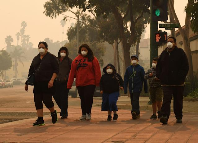 <p>A family wears face masks as they walk through the smoke filled streets after the Thomas wildfire swept through Ventura, California on Dec. 6, 2017. (Photo: Mark Ralston/AFP/Getty Images) </p>