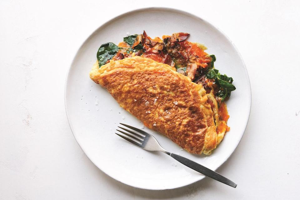 """A porky powerhouse breakfast duo (bacon <em>and</em> sausage) meets mushrooms, cheddar, and spinach in this supremely fluffy diner-style omelet. <a href=""""https://www.epicurious.com/recipes/food/views/pops-double-stuffed-double-fluffed-american-omelet?mbid=synd_yahoo_rss"""" rel=""""nofollow noopener"""" target=""""_blank"""" data-ylk=""""slk:See recipe."""" class=""""link rapid-noclick-resp"""">See recipe.</a>"""