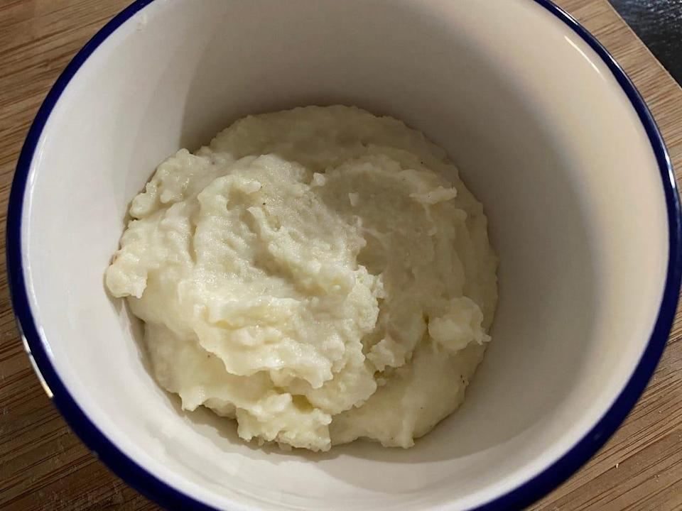 Mashed potatoes in a white bowl.