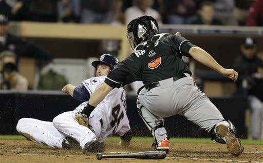 Miami Marlins catcher Brett Hayes, right, is late with the tag on San Diego Padres' Anthony Bass, left, as he slides in safely to home off a hit by Mark Kotsay in the fifth inning during their baseball game Friday, May 4, 2012, in San Diego. (AP Photo/Gregory Bull)
