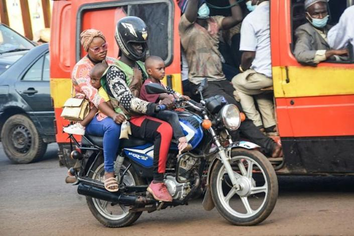 Risky ride: A woman and two young boys take a motorcycle taxi in Conakry
