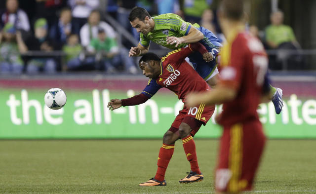 Seattle Sounders' Zach Scott comes down on top of Real Salt Lake's Robbie Findley after they both jumped for a head ball during the first half of an MLS soccer match, Friday, Sept. 13, 2013, in Seattle. (AP Photo/Ted S. Warren)