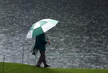 Apr 5, 2017; Augusta, GA, USA; A member stands under an umbrella as the rain falls during the Par 3 Contest at Augusta National Golf Club. Mandatory Credit: Rob Schumacher-USA TODAY Sports