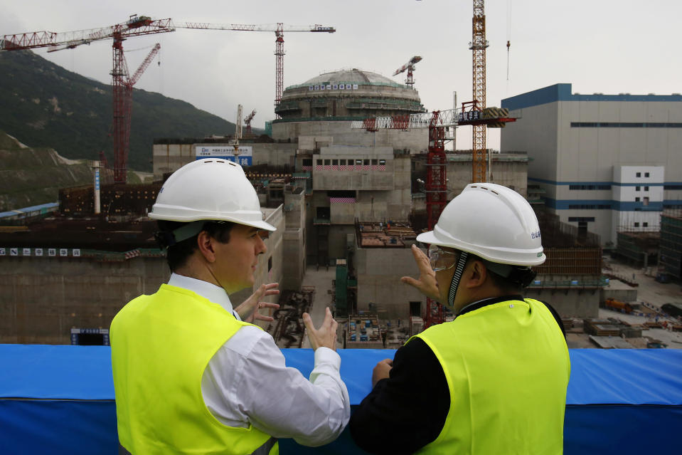 FILE - In this Oct. 17, 2013, file photo, then British Chancellor of the Exchequer George Osborne, left, chats with Taishan Nuclear Power Joint Venture Co. Ltd. General Manager Guo Liming as he inspects a nuclear reactor under construction at the nuclear power plant in Taishan, southeastern China's Guangdong province. The Taishan nuclear plant near Hong Kong suffered five broken fuel rods in a reactor but no radioactivity leaked, the government said Wednesday in its first confirmation of the incident that prompted concern over the facility's safety. (AP Photo/Bobby Yip, Pool, File)