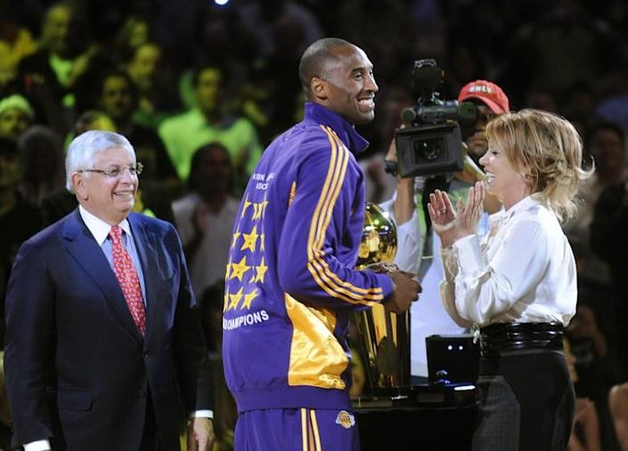 Kobe Bryant smiles after receiving his championship ring from NBA commisioner David Stern, left, and Jeanie Buss on Oct. 27, 2009, at Staples Center.