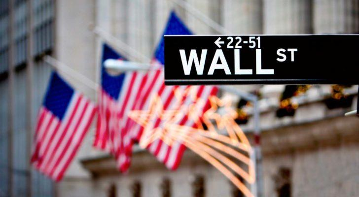 Street sign for Wall Street pictured in front of several American flags representing american stocks