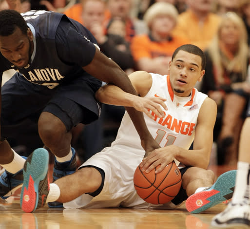 Syracuse's Tyler Ennis, right, and Villanova's Daniel Ochefu, left, battle for a loose ball during the first half of an NCAA college basketball game in Syracuse, N.Y., Saturday, Dec. 28, 2013. (AP Photo/Nick Lisi)