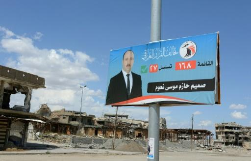 An election campaign poster is seen near destroyed buildings in the former embattled city of Mosul on May 1, 2018 ahead of the upcoming Iraqi parliamentary elections