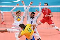 <p>France's Barthelemy Chinenyeze (L) and Earvin Ngapeth (R) block a shot by Brazil's Lucas Saatkamp (C) in the men's preliminary round pool B volleyball match between Brazil and France during the Tokyo 2020 Olympic Games at Ariake Arena in Tokyo on August 1, 2021. (Photo by Anne-Christine POUJOULAT / AFP)</p>