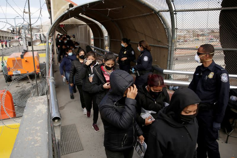FILE PHOTO: Migrants deported from the U.S. walk towards Mexico at the Paso del Norte International border bridge, in this picture taken from Ciudad Juarez