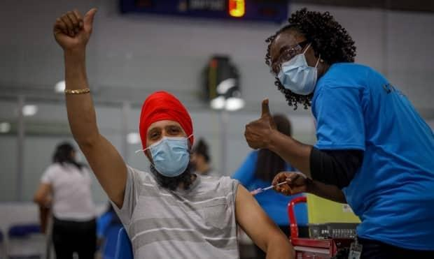 Kulwinder Singh is administered vaccine from Dr. Yvonne Kangong at a pop-up clinic in Calgary.  (Alberta Health Services - image credit)