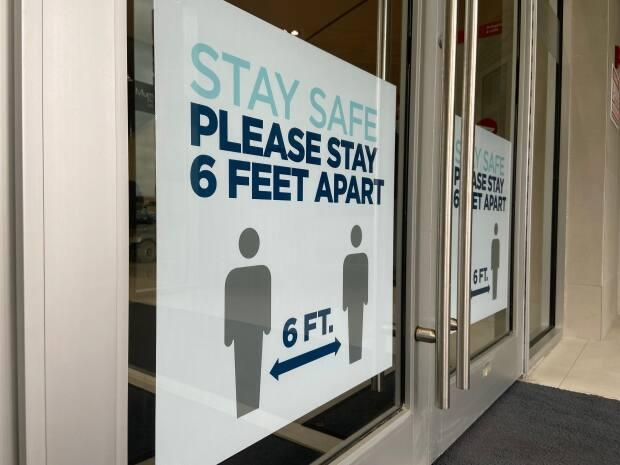 A sign on a door instructs people to stay six feet apart. Nova Scotia reported 25 new cases of COVID-19 on Tuesday. (CBC - image credit)