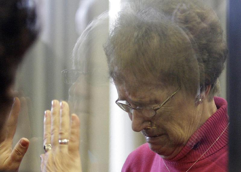 Ruby Klokow, behind glass, reacts to being sentenced to 10 years in prison Wednesday May 1, 2013, in Sheboygan, Wis., for the 1957 death of her six-month-old daughter. Her sister Linda Kimpell, tries to hold her hands through the glass. (AP Photo/The Sheboygan Press, Bruce Halmo)