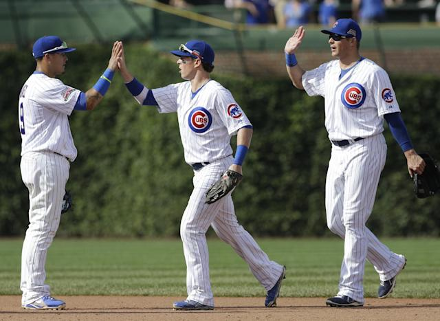 Chicago Cubs' Javier Baez, left, celebrates with teammates Chris Coghlan, center, and Ryan Sweeney after they defeated the Baltimore Orioles 4-1 in an interleague baseball game in Chicago, Friday, Aug. 22, 2014. (AP Photo/Nam Y. Huh)
