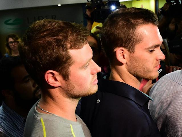 American swimmers Gunnar Bentz (L) and Jack Conger (R) leave the police station at Rio de Janeiro International Airport after being detained on a plane headed back to the US, on August 17, 2016 (AFP Photo/)