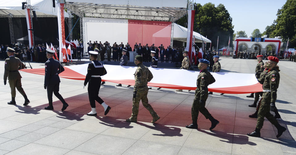 Soldiers carry a large Polish flag as Poland marks the centennial of the Battle of Warsaw, a Polish military victory in 2020 that stopped the Russian Bolshevik march toward the west, in Warsaw, Poland, Saturday, Aug. 15, 2020. U.S. Secretary of State Mike Pompeo attended as he wrapped up a visit to central Europe. (AP Photo/Czarek Sokolowski)