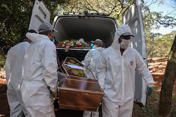 Employees carry the coffin of a person who died from COVID-19 at the Vila Formosa cemetery, in the outskirts of Sao Paulo, Brazil.