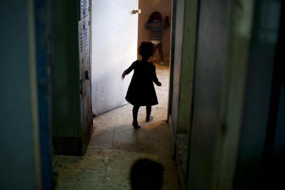 In this Nov. 13, 2013 photo, a young girl walks to her room in the U.S.-based Church of Bible Understanding orphanage in Kenscoff, Haiti. The orphanage is run by a Christian missionary group funded by the Olde Good Things antique store on Manhattan's Upper West Side. While many other orphanages also have failed the Caribbean country's new national standards, and conditions are far worse in some, the group's three-story building on the hilly outskirts of Port-au-Prince stands out because it's run by an organization with such an unusual, and successful fundraising operation. The failure to meet the standards would seem to contradict their financial position.(AP Photo/Dieu Nalio Chery)