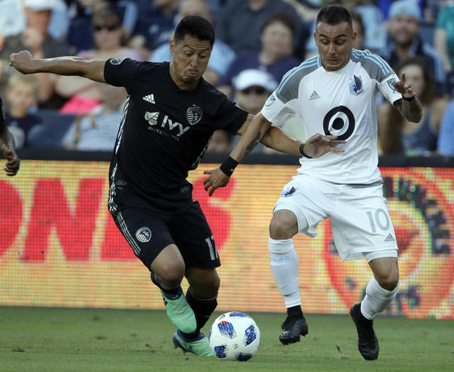 Sporting Kansas City midfielder Roger Espinoza (17) and Minnesota United midfielder Miguel Ibarra (10) converge on the ball during the first half of an MLS soccer match in Kansas City, Kan., Sunday, June 3, 2018. (AP Photo/Orlin Wagner)