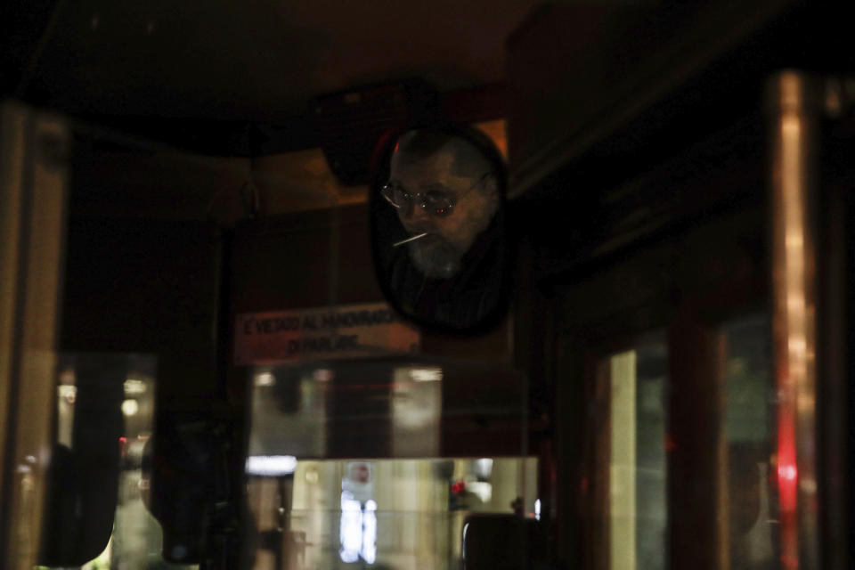 A streetcar driver is reflected in a mirror, top right, as he drives around Milan, northern Italy, early Sunday, Oct. 25, 2020. Since the 11 p.m.-5 a.m. curfew took effect last Thursday, people can only move around during those hours for reasons of work, health or necessity. (AP Photo/Luca Bruno)