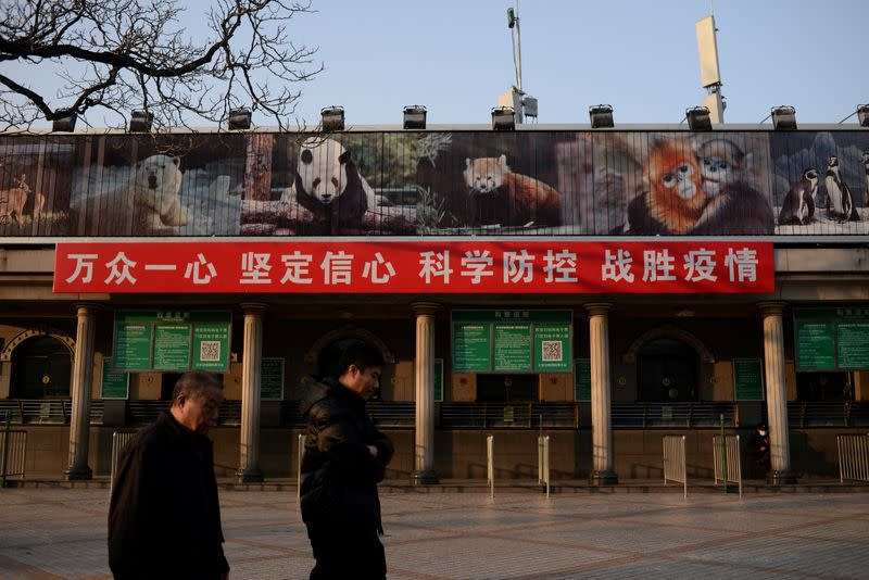 FILE PHOTO: Men walk past a banner hung on the ticket office of the Beijing Zoo that is closed following an outbreak of the novel coronavirus in the country, in Beijing