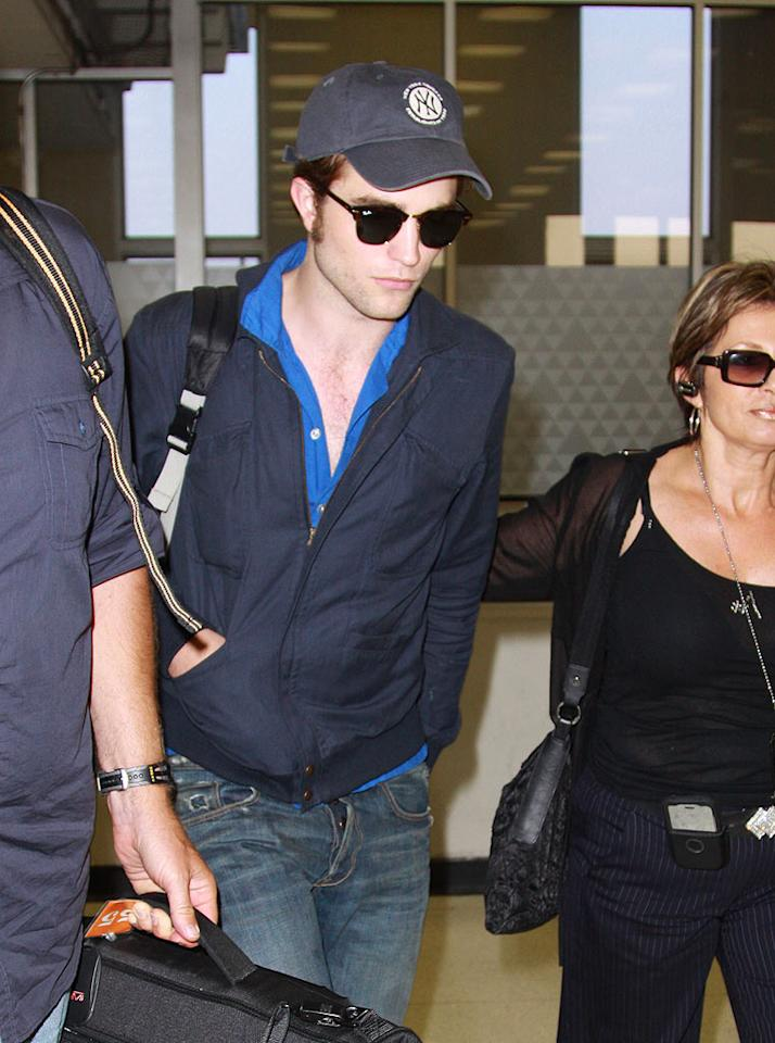 """You can try to hide behind sunglasses and a hat, Robert Pattinson, but as long as you're exposing that vampire-like pasty white skin, other travelers at JFK Airport are gonna notice you! <a href=""""http://www.infdaily.com"""" target=""""new"""">INFDaily.com</a> - July 22, 2009"""