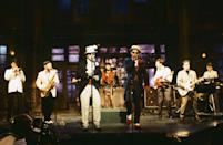"THEN: (L-R) Lee Thompson, Chas Smash, Suggs, Mark Bedford, Chris Foreman, Mike Barson of musical guest Madness perform on ""Saturday Night Live"" on April 14, 1984. (Photo by: Al Levine/NBC/NBCU Photo Bank)"