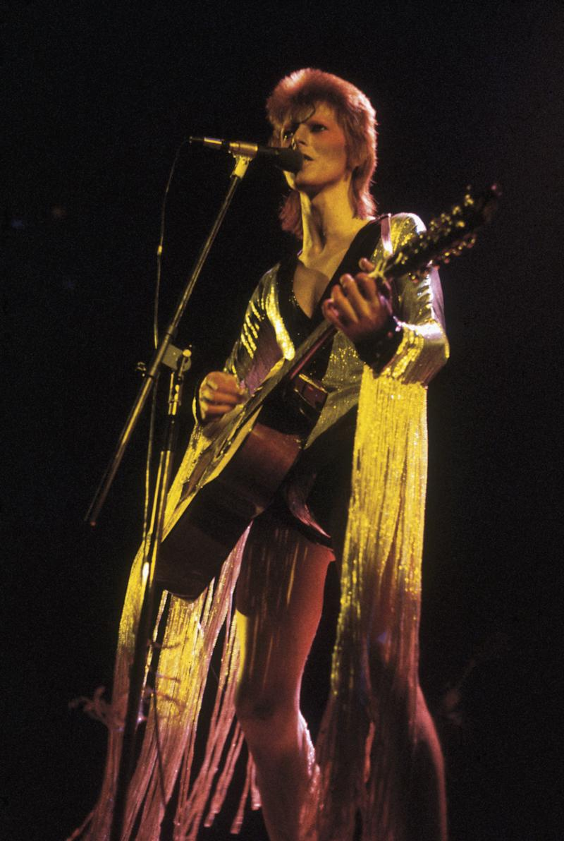 David Bowie performing as Ziggy Stardust at the Hammersmith Odeon, 1973. He is wearing a silver costume with gold tassels by Japanese designer Kansai Yamamoto. (Photo by Debi Doss/Hulton Archive/Getty Images)