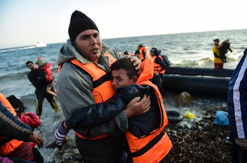 People react after arriving on the Greek island of Lesbos on November 17, 2015, after crossing the Aegean Sea from Turkey