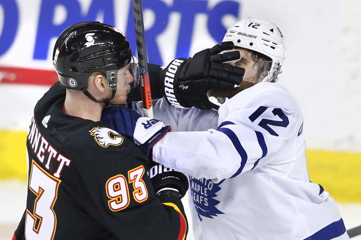 Toronto Maple Leafs' Alex Galchenyuk, right, gets a face wash from Calgary Flames' Sam Bennett during the third period of an NHL hockey game, Monday, April 5, 2021, in Calgary, Alberta. (Larry MacDougal/The Canadian Press via AP)
