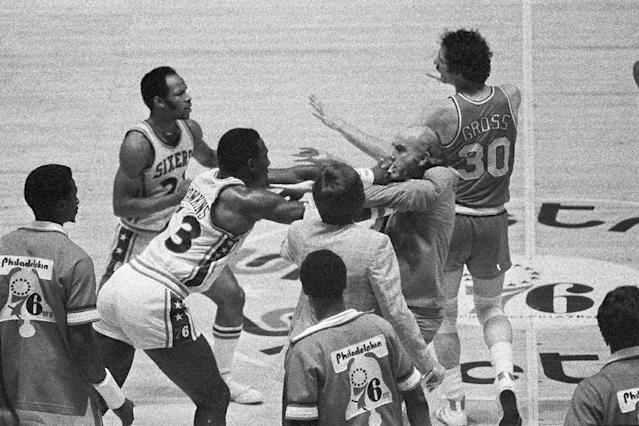 FILE - In this May 26, 1977, file photo, Philadelphia 76ers' Darrell Dawkins shoves Portland Trail Blazers coach Jack Ramsay after Ramsay tried to break up a fight on the floor between Dawkins and several other Blazers during the NBA basketball playoffs in Philadelphia. Ramsay, a Hall of Fame coach who led the Portland Trail Blazers to the 1977 NBA championship before he became one of the league's most respected broadcasters, has died following a long battle with cancer. He was 89. (AP Photo/Gene Puskar, File)