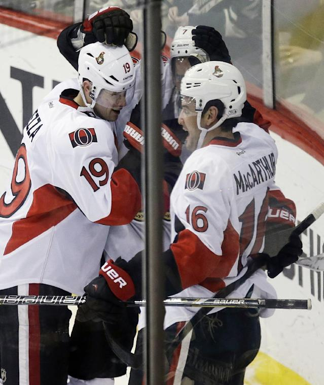 Ottawa Senators' Clarke MacArthur, right, is congratulated by Jason Spezza, left, and Kyle Turris, after MacArthur scored a power play goal against Minnesota Wild goalie Darcy Kuemper in the first period of an NHL hockey game, Tuesday, Jan. 14, 2014, in St. Paul, Minn. (AP Photo/Jim Mone)