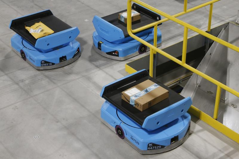 """In this Dec. 17, 2019, photo Amazon robots move along the warehouse floor with packages before finding the proper delivery chute, transporting packages from workers to chutes that are organized by zip code, at an Amazon warehouse facility in Goodyear, Ariz. Amazon and its rivals are increasingly requiring warehouse employees to get used to working with robots. The company now has more than 200,000 robotic vehicles it calls """"drives"""" that are moving goods through its delivery-fulfillment centers around the U.S. (AP Photo/Ross D. Franklin)"""